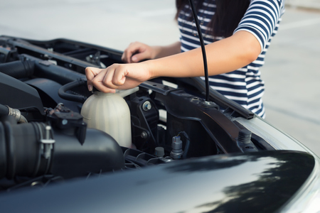 coolant: Women checking coolant level of car.