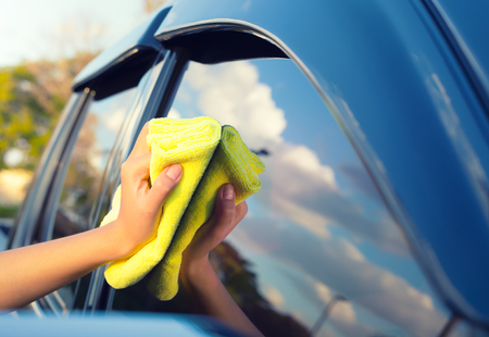 cloths: Womens hand wiping on glass of car.