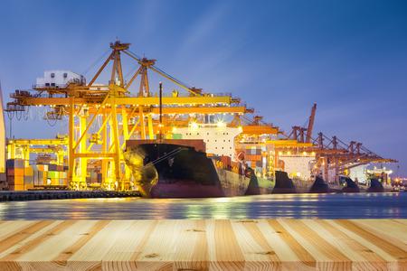 Vrachtschip het werken met kraan in de haven, schemering tijd. Stockfoto