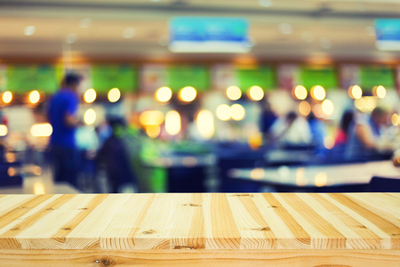 Defocused and blur image of food court and wood table.