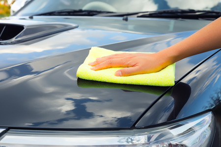 surface: Girls hand wiping on surface of car. Stock Photo
