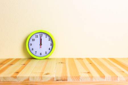 white face: Clock on wood table with concrete wall background. Stock Photo