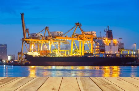 貨物船と港でクレーンが反省する川、黄昏時。