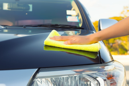 wiping: Girls hand wiping on surface of car shine.