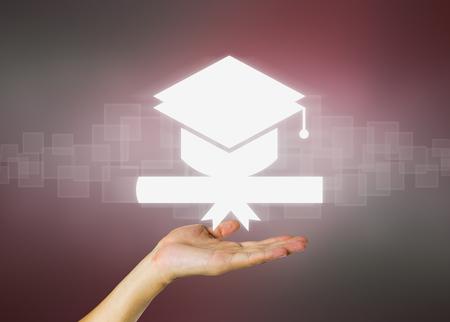 hand holding: Concept of graduation in dark background.