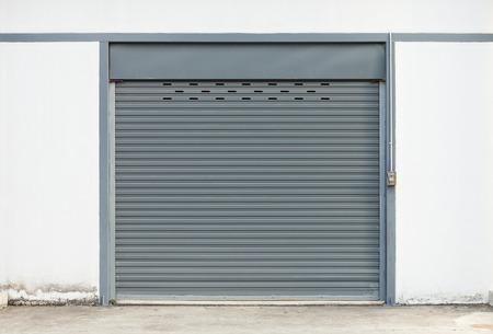 edificio industrial: obturador puerta exterior del edificio, de color gris.