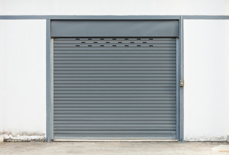 metal wall: Shutter door outside building, gray color.