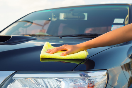 Girls hand wiping on surface of car. Stock Photo