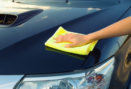 car glass: Girls hand wiping on surface of car. Stock Photo