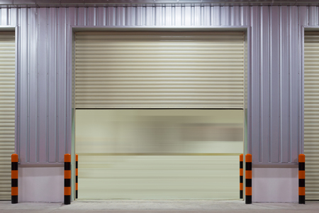 building color: Shutter door outside building, beige color.