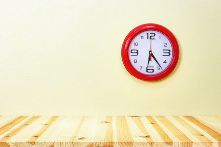 Clock and wood table with concrete wall background.
