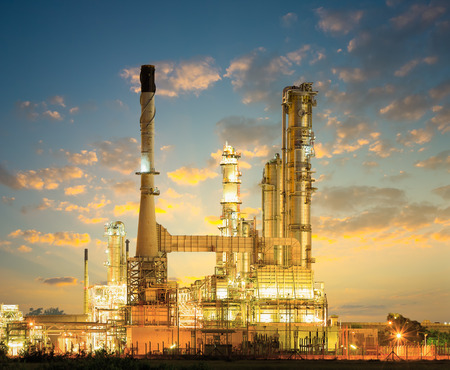 Olieraffinaderij bij schemer met donkere hemel achtergrond.