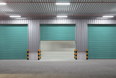 Shutter door or roller door and concrete floor outside factory building use for industrial background. Stock Photo