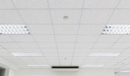 Sufit i oświetlenie wewnątrz budynku biurowego.