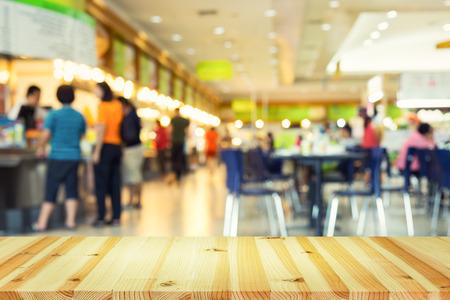 desenfocado la foto borrosa o del patio de comidas y mesa de madera de primera utilización para el fondo.