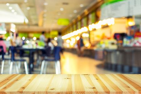 desenfocado la foto borrosa o del patio de comidas y mesa de madera de primera utilización para el fondo. Foto de archivo
