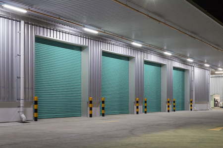 Shutter door or roller door and concrete floor outside factory building use for industrial background. Фото со стока
