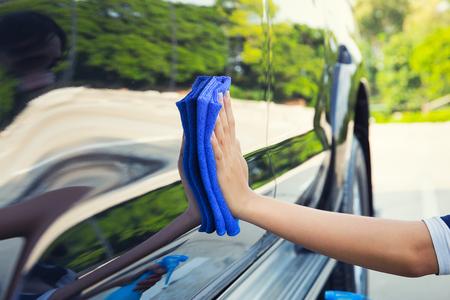 La mano de la mujer asiática que limpia la superficie del coche por el paño de microfibra.