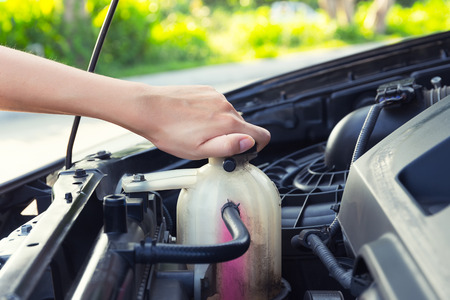 Asian girl's hand checking level of coolant car engine. Imagens