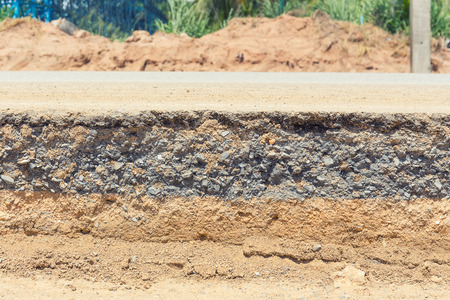gravel: Cross section of asphalt road with blue sky background. Stock Photo