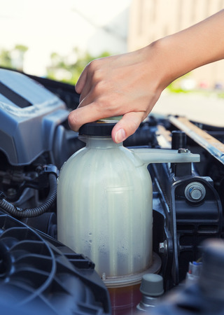 coolant: Asian girls hand checking level of coolant car engine.