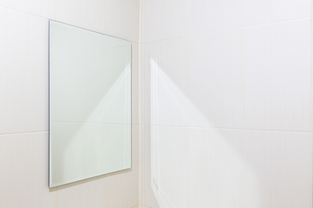 bathroom wall: Mirror and white tile wall in bathroom.