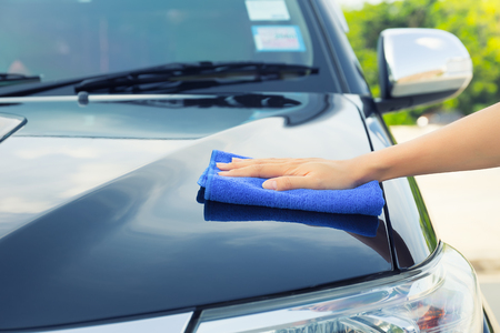 cloth fiber: Asian womans hand wiping surface of car by micro fiber cloth.
