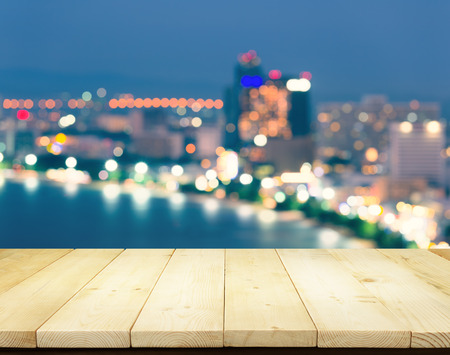 Bokeh blurred of Pattaya city at night montage with wood table top for background. Stock Photo