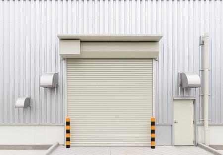 shutter door: Shutter door or roller door and concrete floor outside factory building use for industrial background. Stock Photo