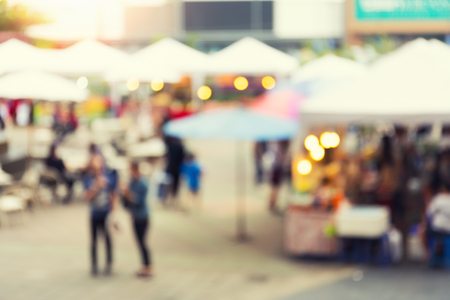 food court: Blurred photo of food exhibition fair with many people at twilight time for background. Stock Photo