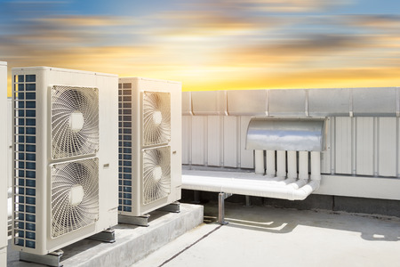 industry: Air compressor machine part of air conditioner system on roof deck with sky background.