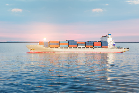 Cargo freight ship and cargo container in sea with sky for logistics and transportation background.