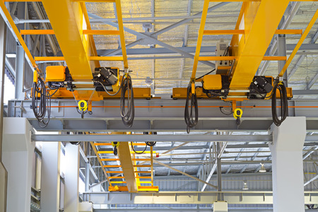 overhead crane: Overhead crane and hook inside factory building for lifting work.