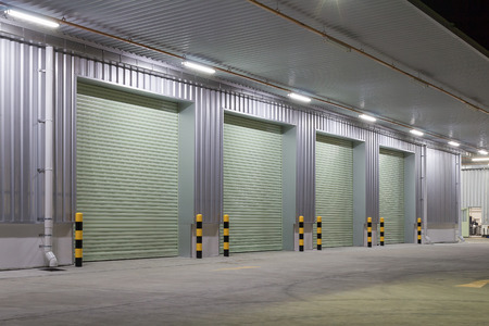 roller: Shutter door or roller door and concrete floor outside factory building use for industrial background. Stock Photo