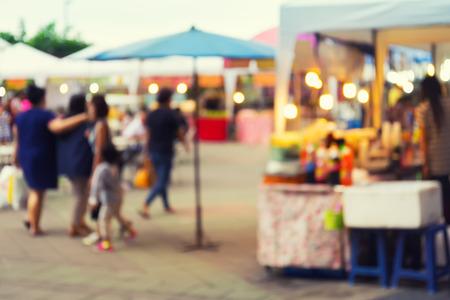 outdoor: Foto borrosa de feria de exposición de alimentos con mucha gente en el tiempo de crepúsculo para el fondo. Foto de archivo