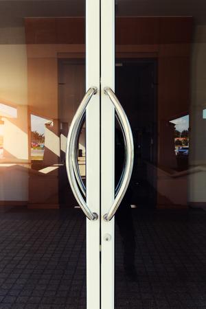 handle bars: Chrome door handle and glass of aluminium door outside building. Stock Photo