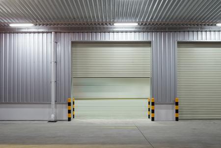 portones: puerta de persiana o puerta giratorio y el piso de concreto fuera de la fábrica de usos de fondo industrial.