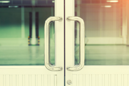 door knob: door handle and glass of aluminium door inside building.