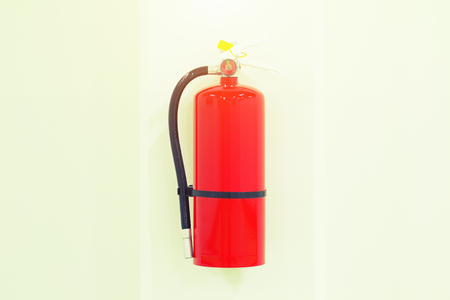 suppression: Emergency safety equipment or  fire extinguisher on concrete wall inside room, red color.