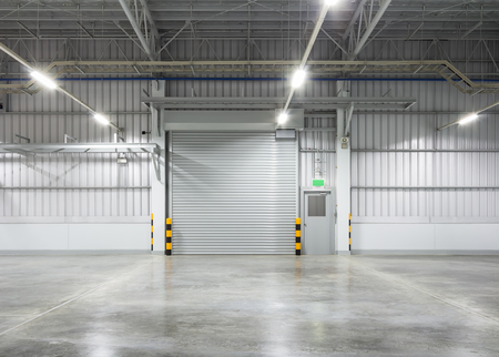 Roller shutter door and concrete floor inside factory building for industy background.