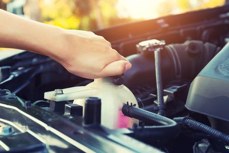 Asian girl's hand checking level of coolant car engine. Foto de archivo