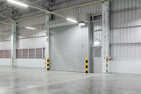 Roller shutter door and concrete floor outside factory building for industry background.