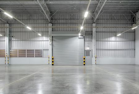 롤러 셔터 문 및 산업 배경에 대 한 공장 건물 외부의 콘크리트 바닥.