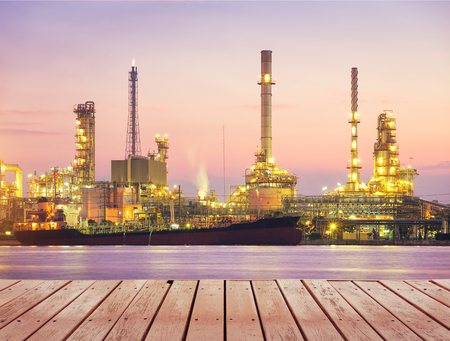 Oil refinery factory montage with wood table top at twilight with sky background. Stock Photo