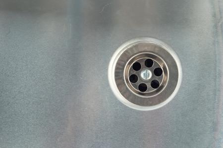 sink: Water drain hole in stainless steel sink.