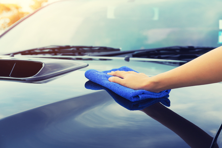 gloss: Asian womans hand wiping surface of car by micro fiber cloth.