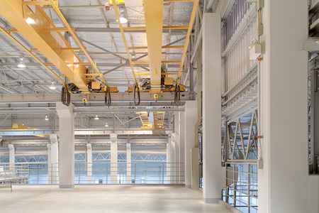 Overhead crane and concrete floor inside factory building for background. 스톡 콘텐츠
