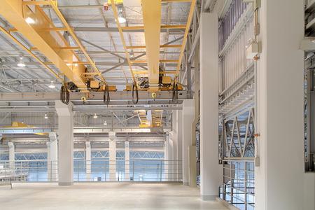 Suwnica i betonowa podłoga wewnątrz budynku fabryki na tle. Zdjęcie Seryjne