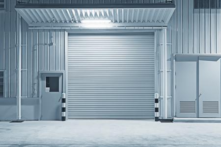 Rollladentür und Betonboden außerhalb des Fabrikgebäudes für Industriehintergrund. Standard-Bild