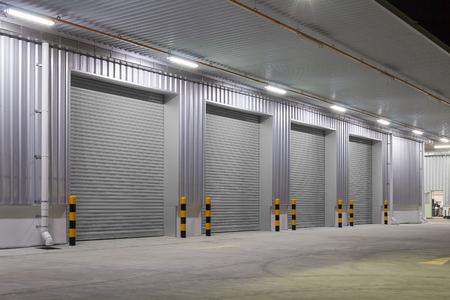 Rolltor oder Rolltor und Betonboden außerhalb des Fabrikgebäudes für den industriellen Hintergrund.
